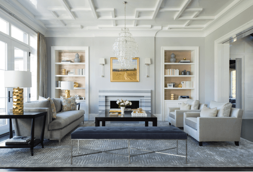 Transitional living room designed with a gold frame art piece and home decors fitted on the built-in shelves. It includes a lovely crystal chandelier that hung from the stylish coffered ceiling.