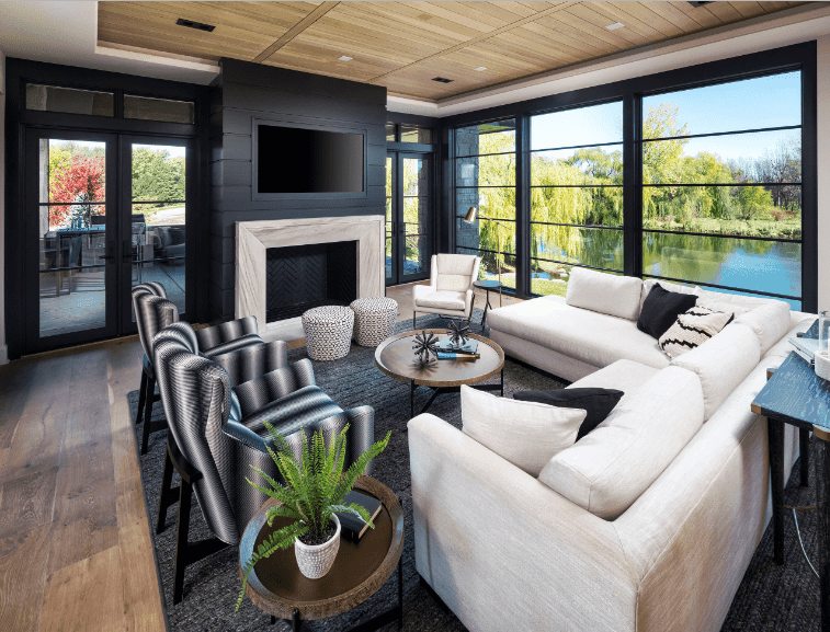 Black living room with a wood plank ceiling that complements with the hardwood flooring. It is surrounded by glass windows with stunning outdoor scenery.
