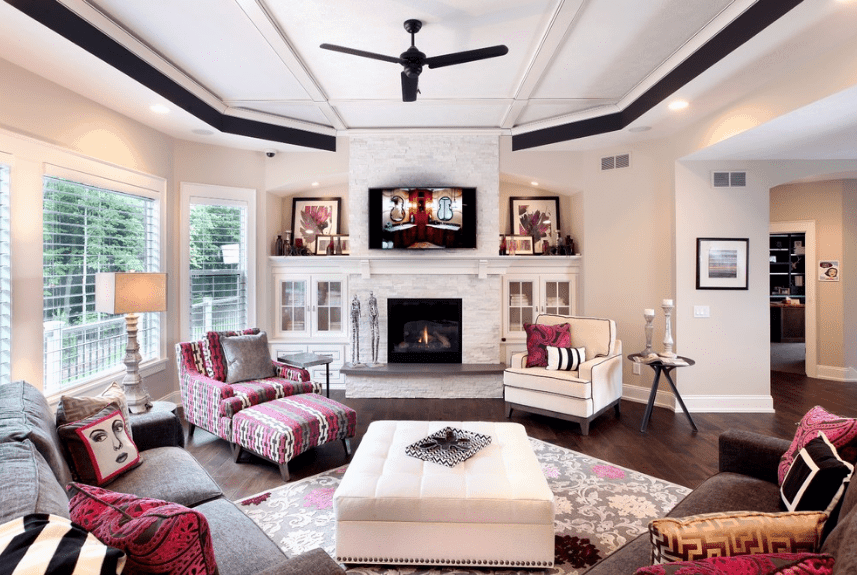 Gorgeous living room styled with an amazing wall art fixed on the pillar above the fireplace. It has hardwood flooring topped with a black floral patterned rug where a white ottoman sits.