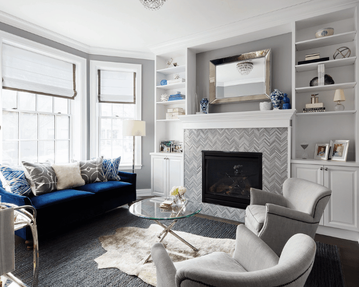 A blue velvet sofa with multi-colored pillows stands out in this gray living room. It is paired with wingback chairs and a round glass top table that sits on layered rugs.
