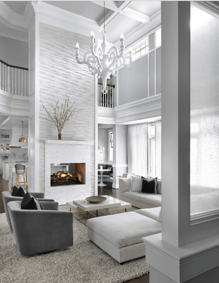 White living room boasts a high coffered ceiling and an oversized candle chandelier. There's also a marble fireplace fixed to the white textured pillar.