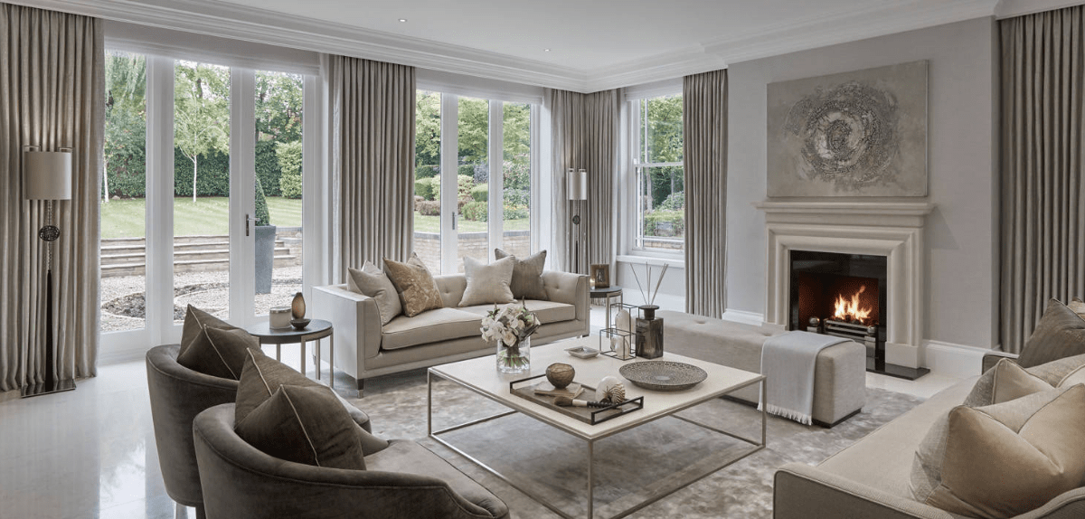 Elegant living room surrounded with floor to ceiling glass windows dressed in gray draperies. It is decorated with an interesting wall art canvas mounted above the fireplace.