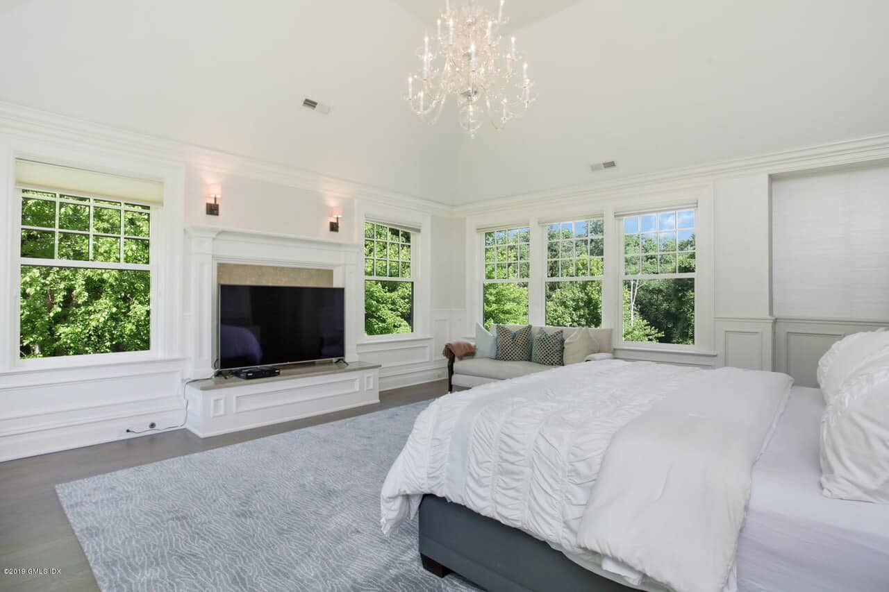 The white cove ceiling of this primary bedroom is paired with the bright white walls filled with windows that feature the lush greenery outside that serves as a nice background and light source for the white cottage bed complemented by the white chandelier.