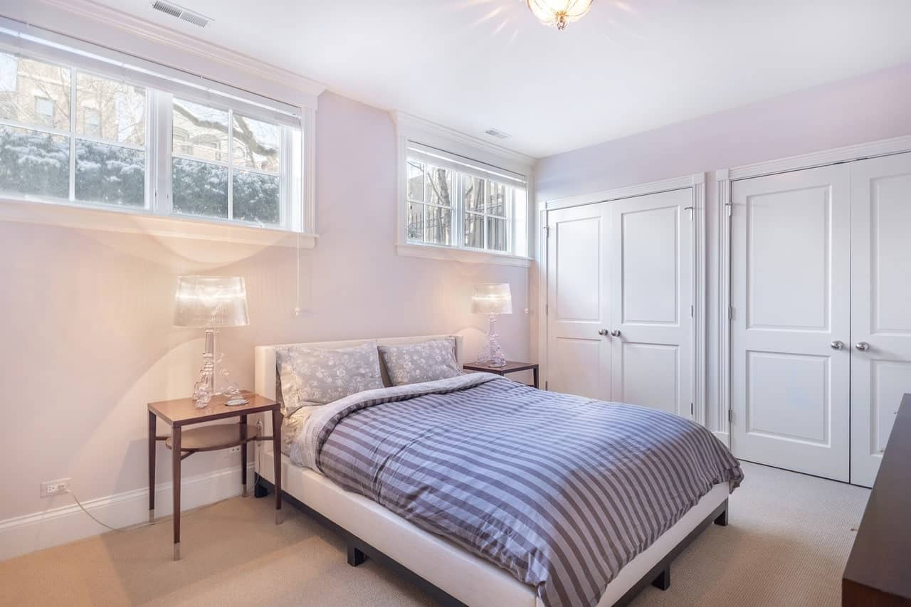 This is a simple bedroom with a cottage bed that has striped gray sheets and a white frame that matches with the light hues of the walls and ceiling contrasted by a beige carpeted flooring brightened by modern table lamps on the bedside tables.