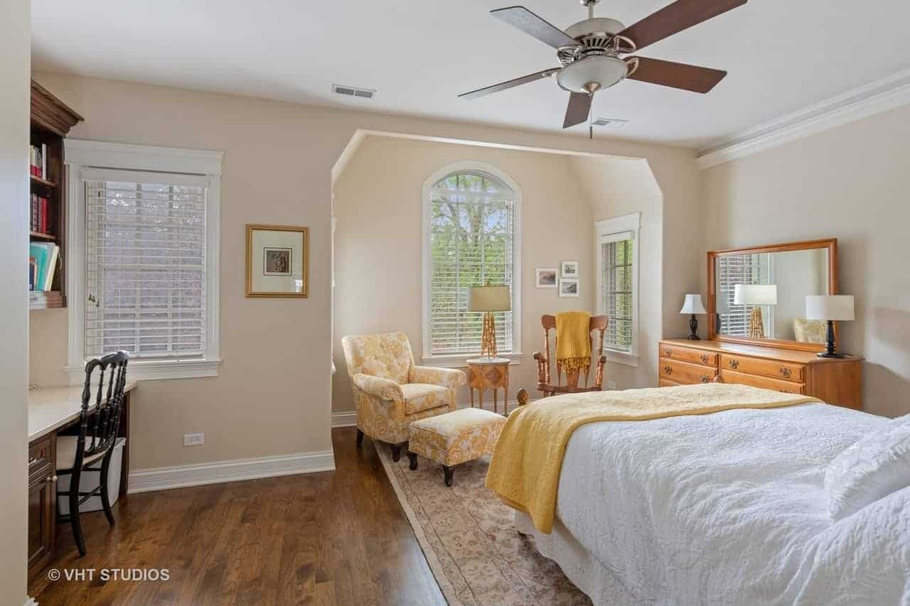 The traditional bed is paired with a charming sitting area by its foot that has a yellow floral cushioned armchair and a wooden rocking chair in an alcove of arched windows and beige walls.