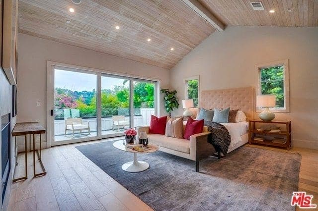 This master bedroom has a high wooden ceiling that has a single exposed wooden beam running in the middle. The beige cushioned headboard of the traditional bed suits this aesthetic contrasted by the large gray area rug.