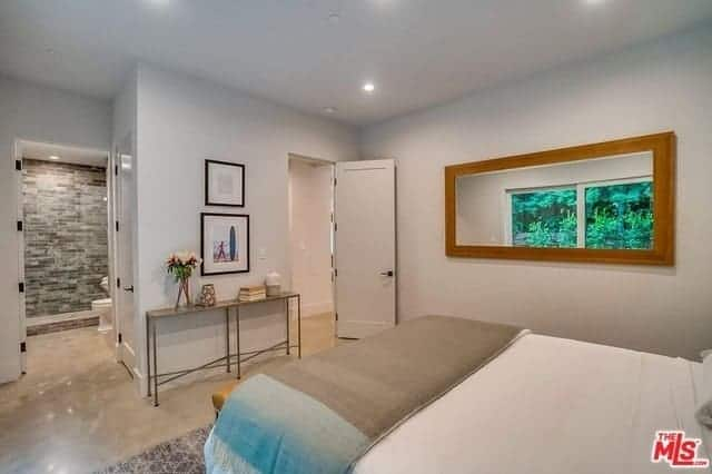 This simple bedroom has a wall-mounted mirror on the side of the bed's gray wall that matches with gray ceiling that makes the white sheets of the traditional bed stand out against the hardwood flooring.