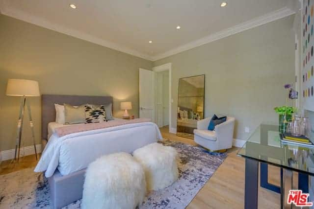 The hardwood flooring of this master bedroom is topped with a gray industrial area rug that fits with the gray frame of the traditional bed flanked by a standing lamp on the left side and a table lamp on the right side on a bedside table.