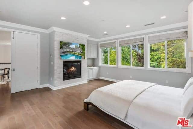 The gray walls of this master bedroom has a fireplace inlaid in gray stone with white molding that contrasts the hardwood flooring brightened by the row of windows beside the traditional bed with a wooden frame.
