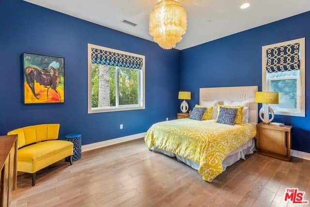 This delightful primary bedroom has a colorful palette of mixed blue walls and yellow elements in the patterned yellow bed sheet, pillows, table lamps as well as the cushioned bench by the corner beneath the wall-mounted artwork.