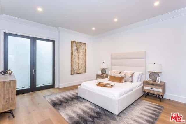 The white traditional bed has a tall cushioned headboard that blends in with the white walls flanked by wooden bedside drawers bearing table lamps with white hood. The hardwood flooring is a nice pairing for the gray patterned area rug under the bed.