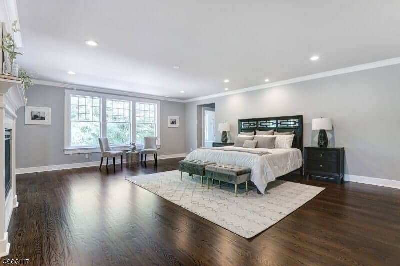 This is a spacious primary bedroom that has dark hardwood flooring topped with a white patterned area rug under the traditional bed that has a black wooden headboard matched with black bedside drawers.