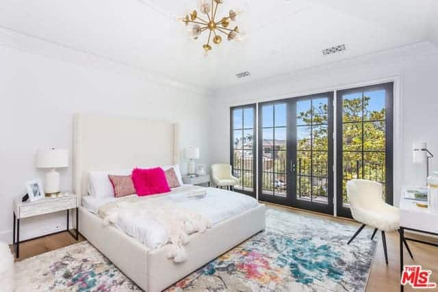 The white cove ceiling and walls are accented with a splash of color from the colorful area rug underneath the white bed that has a tall cushioned headboard that contrasts the dark frames of the French glass doors.