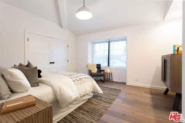 This cozy and simple Transitional-Style bedroom has a white cottage bed paired with a lovely sitting area by the wide window with a black leather armchair with wooden legs that blend with the hardwood flooring.