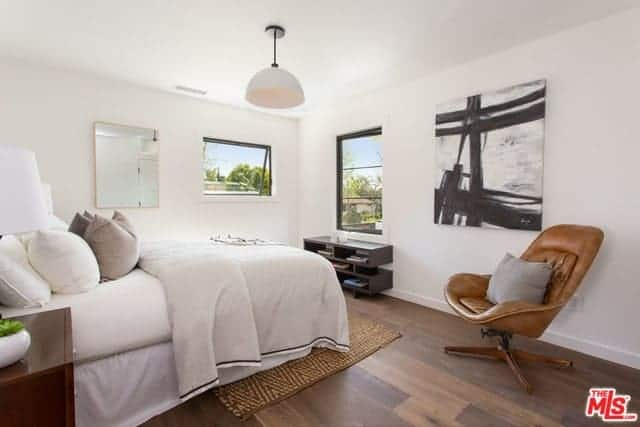 The swivel chair that has a brown leather finish stands out against the white walls of this Transitional-Style bedroom that is accented with a wall-mounted black and white painting that fits with the white bed.