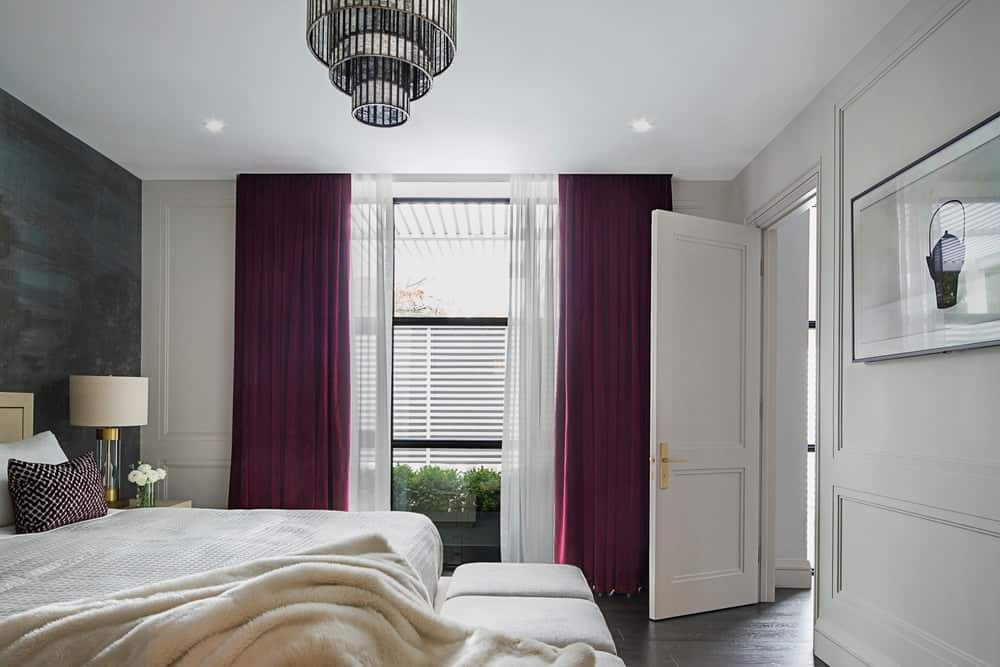 The brilliant purple curtains flanking the tall window stands out against the white walls and ceiling that supports a charming semi-flush mount lighting over the white sheets of the bed that is backed into a black wall.