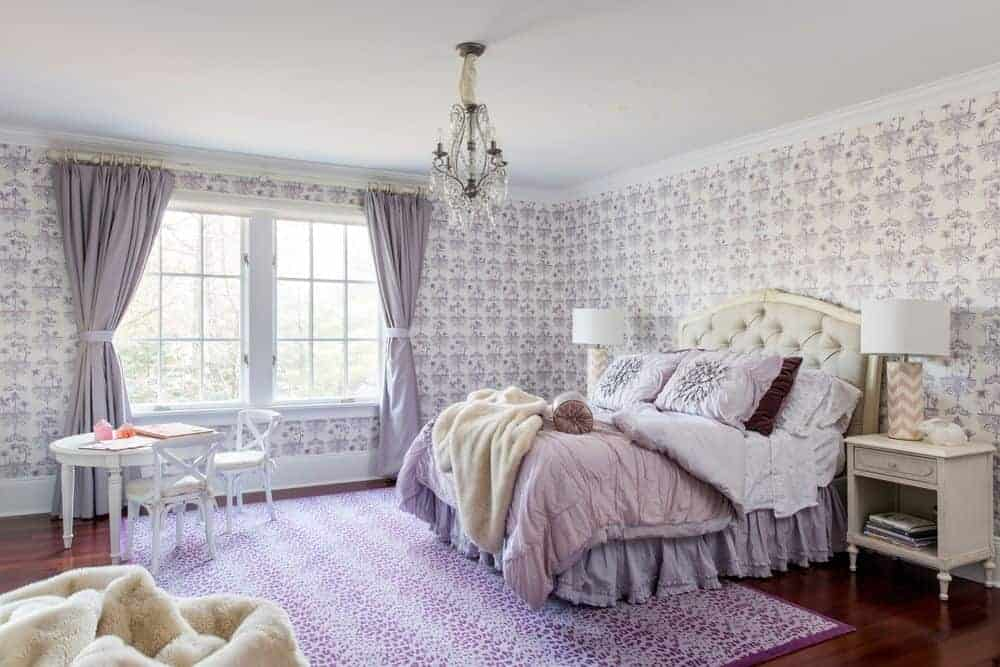 This chic Transitional-Style bedroom has purple patterned wallpaper dominating the walls matching with the purple patterned area rug over the dark hardwood flooring that contrasts the beige cushioned headboard of the traditional bed.