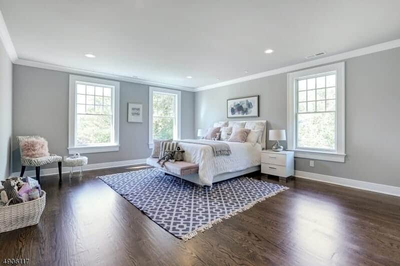 This chic bedroom that has light gray walls and ceiling is brightened by the natural lights of the large windows. The contrast here comes from the dark hardwood flooring topped with a blue patterned area rug.