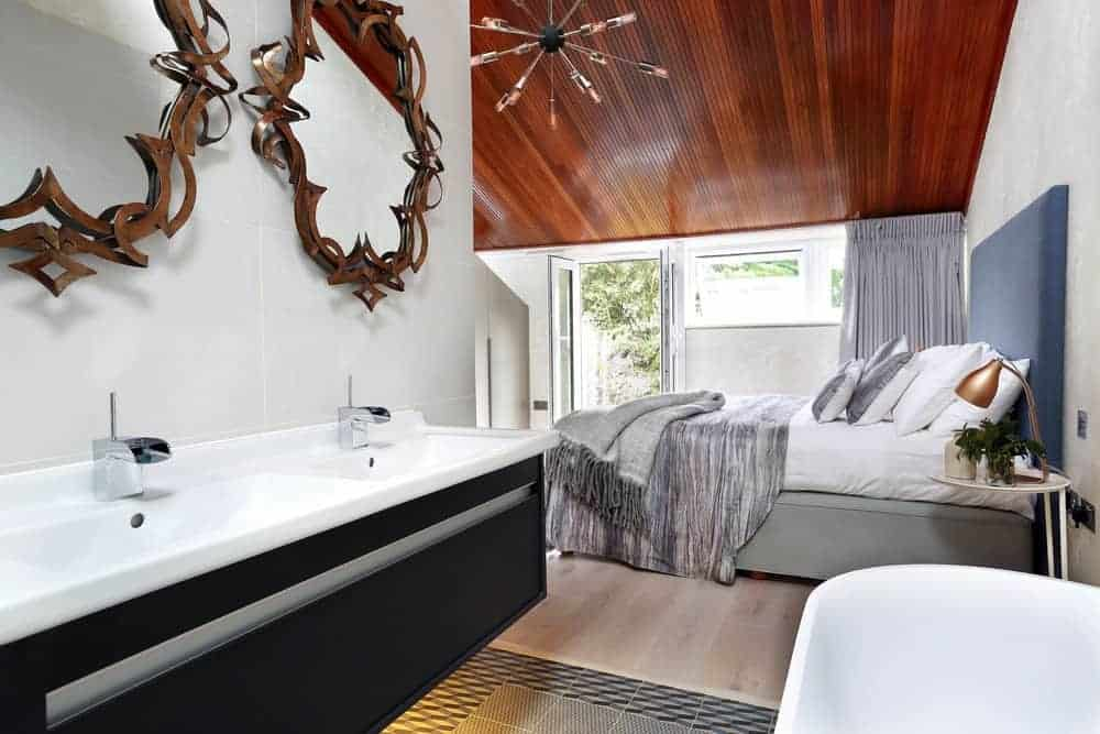 This bedroom is open to the bathroom separated by bathroom floor tiles that transition from the light hardwood flooring of the bedroom that has a bed with a tall blue cushioned headboard complemented by a wooden ceiling.