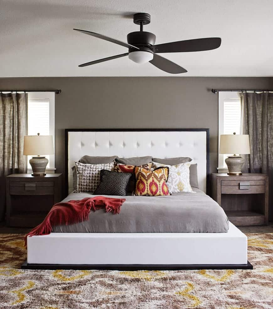 The gray walls and wooden bedside tables makes the white cushioned headboard of the platform bed stand out. This contrasts the colorful area rug over the hardwood flooring as well as the black modern ceiling fan with a light on it.