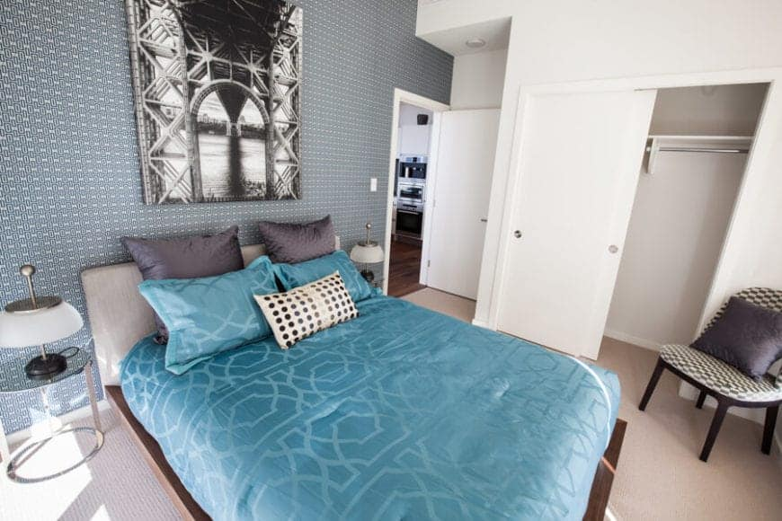 The green patterned wall behind the gray cushioned headboard of the bed fits well with the patterned green comforter of the bed that is flanked with glass-top modern bedside tables with modern table lamps.