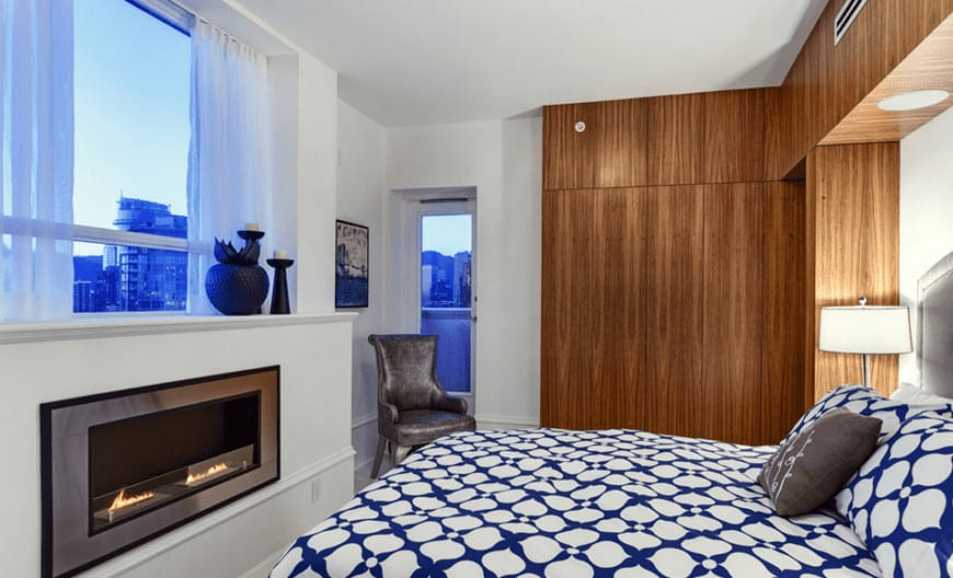 The blue patterns of the bed sheet is illuminated by the natural light coming in from the window by the foot of the bed that has a modern fireplace inlaid in white contrasting the wooden walls by the head of the bed.