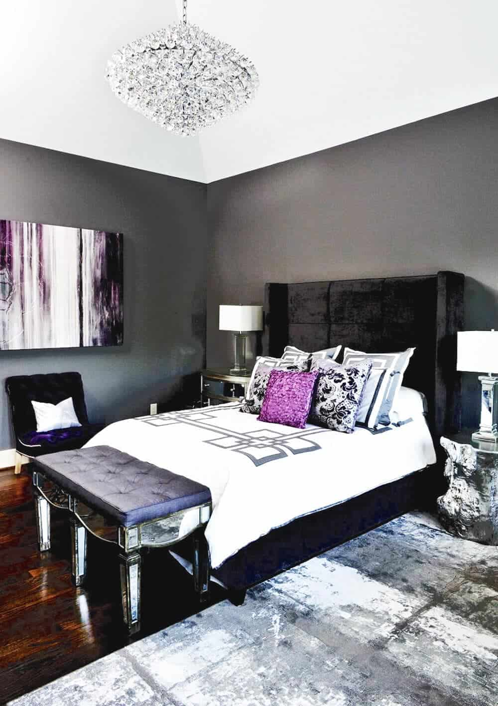 The black velvet frame and headboard of the bed as well as the dark walls are contrasted by the sleek and shiny silver bedside tables, lamps and the cushioned bench at the foot of the bed that matches with the crystal pendant light.