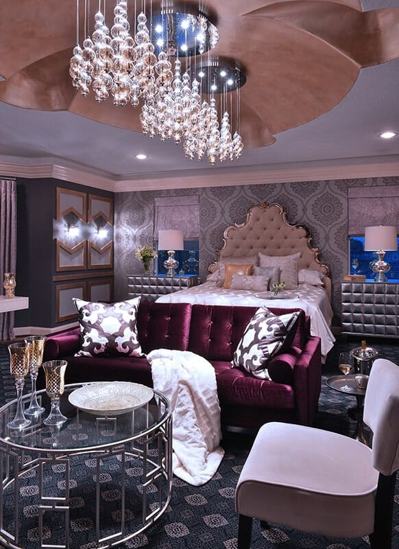 This lavish Transitional-Style primary bedroom is filled to the brim with elegant patterns and details that complement each other like the green patterned walls and the elegant beige headboard as well as the deep purple sofa by the foot of the bed.