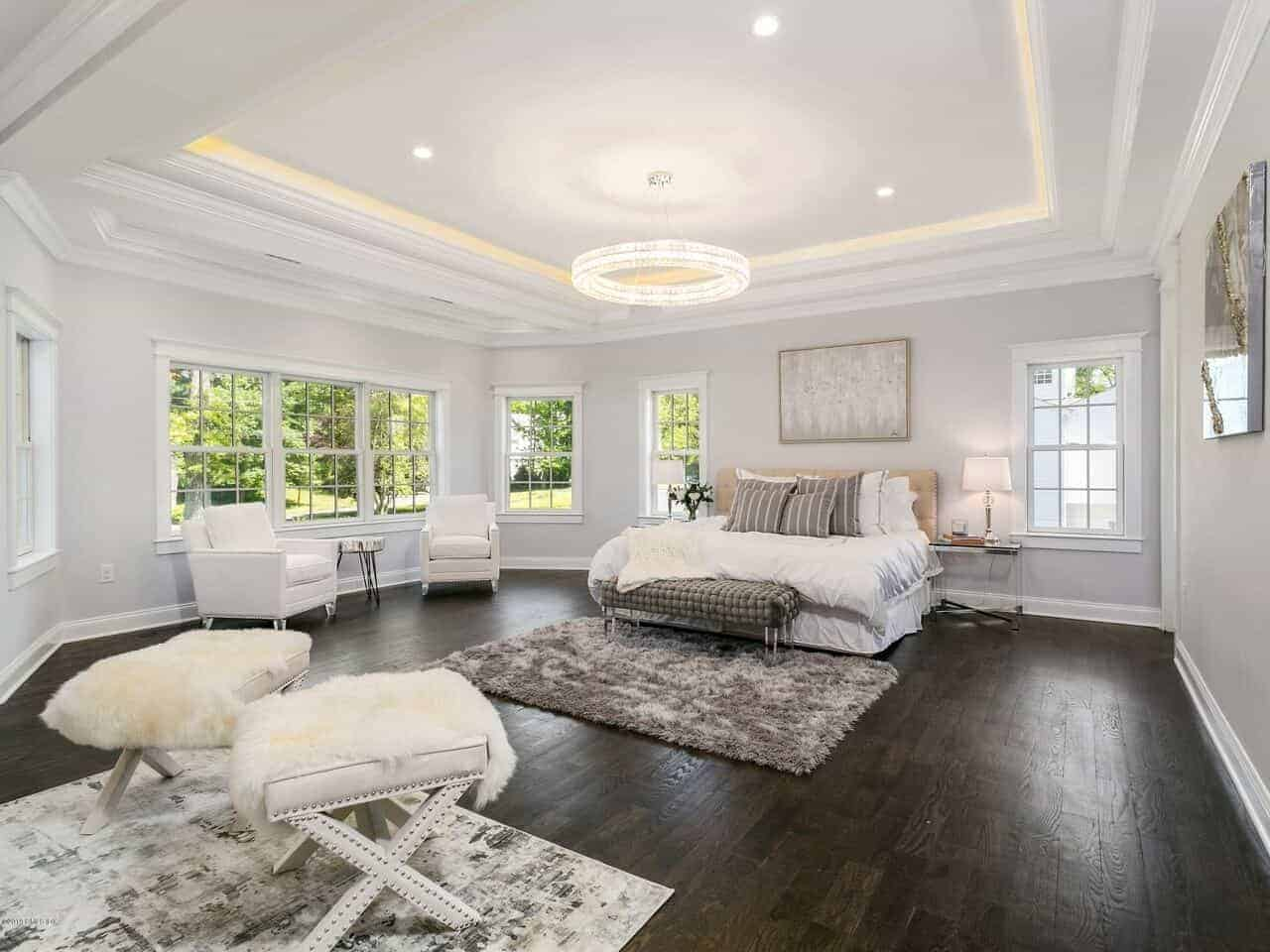 This primary bedroom has a brilliant modern circular light hanging from the white tray ceiling that contrasts the dark hardwood flooring that makes the white bed stand out with its beige cushioned headboard.