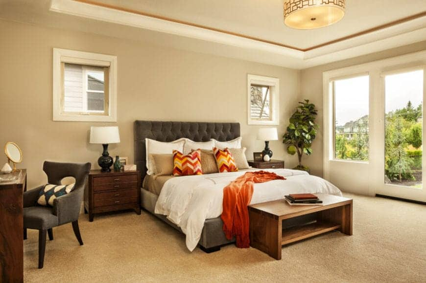 The beige tray ceiling is trimmed with an orange detail that pairs well with the orange sheet and pillows that bring in a dash of color to the beige walls and carpeted flooring contrasted by the dark gray cushioned headboard of the traditional bed.