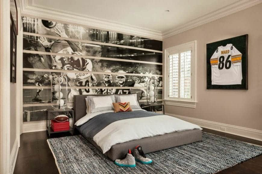 The wall at the behind of the bed is dominated by a large black and white photo of a football moment used as a nice background for the pair of modern table lamps on the bedside tables flanking the gray platform bed over a gray area rug covering the hardwood flooring.