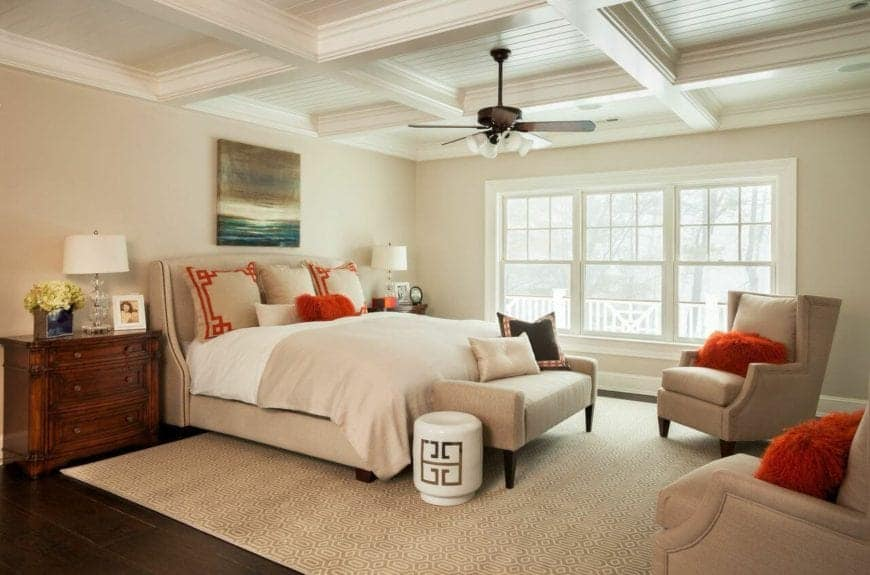 The white coffered ceiling is accented by a dark ceiling fan that hangs over the sitting area by the foot of the beige bed that has beige cushioned chairs over a beige area rug that covers the dark hardwood flooring.