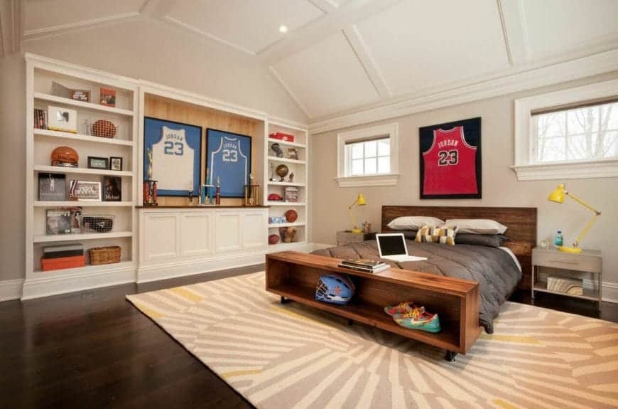 The white cove ceiling has a white wooden finish that matches well with the white wooden structure dominating a wall that has built-in shelves and trophy display beside the wooden bed that is contrasted by the light gray area rug over the dark hardwood flooring.