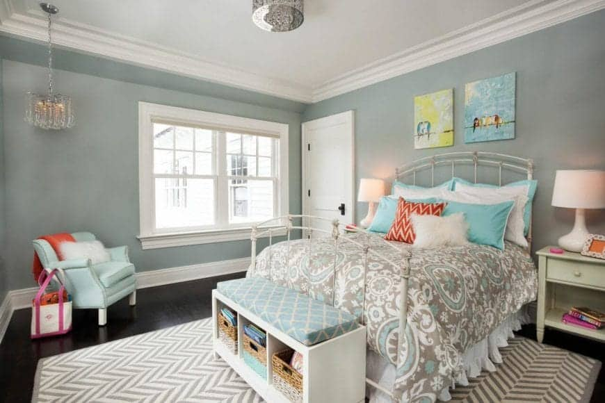 This lovely Transitional-Style bedroom has green walls accented by the pair of colorful paintings mounted on the wall above the white railing of the headboard of the bed that has a gray bedsheet pairing with the area rug.