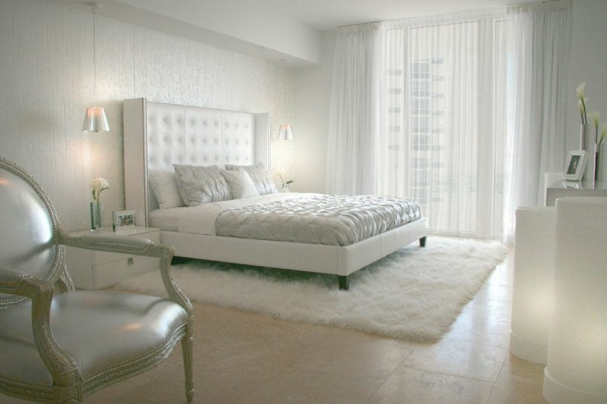 This icy white bedroom has beige marble flooring topped with a white furry area rug that looks like fog beneath the white bed that has a large white cushioned headboard flanked with silvery pendant lights over modern white bedside drawers.
