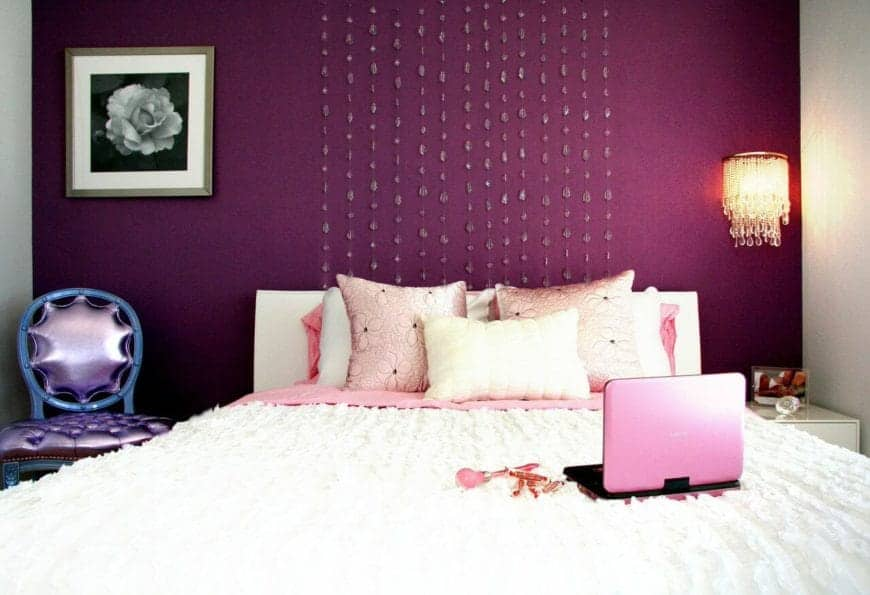 The white traditional bed that has a white headboard is backed against a deep purple wall adorned with crystals above the headboard as well as a framed painting of a rose and a wall-mounted crystal lamp above the bedside drawer.