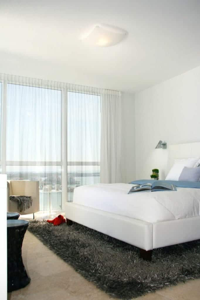 The white walls and white ceiling are well matched with a beige marble flooring that is covered with a gray furry area rug that is illuminated by the curtains tall windows that also brighten up the white bed.
