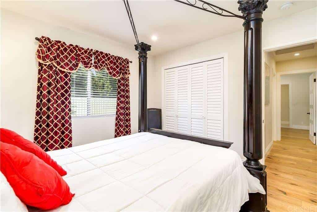 This intimate bedroom is dominated by a dark wooden four-poster bed that has white sheets and orange pillows that fit with the aesthetic of the red patterned curtain against the white walls and ceiling.