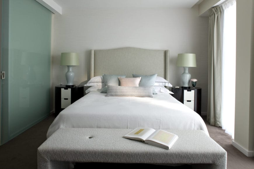 The gray carpeted floors of this Transitional-Style bedroom is complemented by the white sheets of the bed that has a beige cushioned headboard that pairs well with the hoods of the table lamps flanking it.