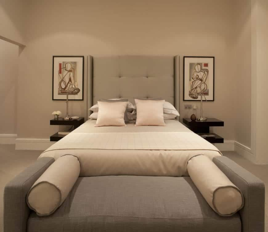 The beige walls of this primary bedroom is a nice background for the gray cushioned headboard of the traditional bed that has two black bedside tables topped with wall-mounted abstract artworks.
