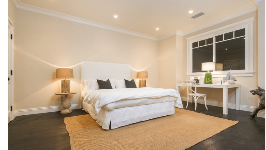 The cheerful yellow walls and ceiling have white molding that contrasts the dark hardwood flooring paired with a rustic woven area rug that is reflected by the aesthetic of the bedside tables and lamps.