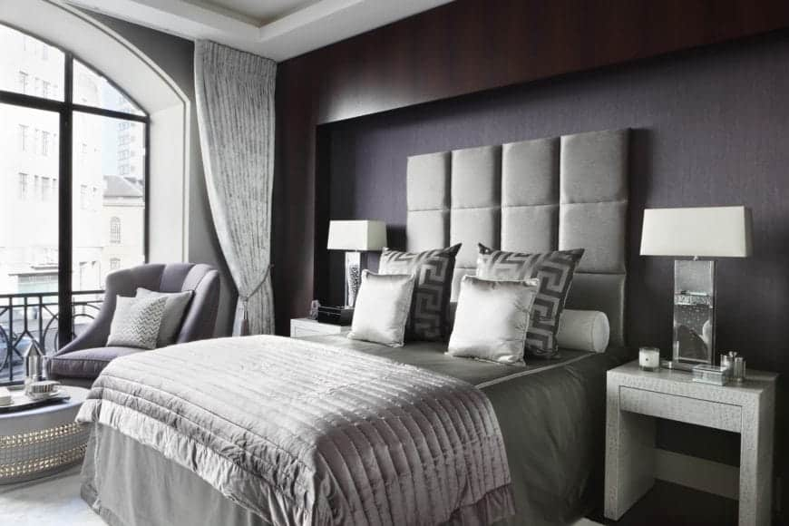 The sleek and silver bedsheets and silver cushioned headboard of the bed contrasts the black wall behind with a dark wooden border that contrasts the white tray ceiling brightened by the large arched window beside the bed.