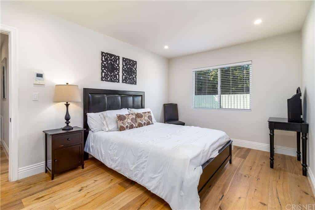 This simple bedroom has a light hardwood flooring that is contrasted by the dark wooden traditional bed with a black cushioned headboard that stands out against the light gray walls and ceiling adorned with black artworks.