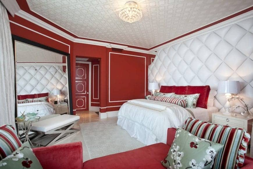 This Transitional-Style primary bedroom has red walls trimmed with white that blends in with the white patterned flooring and white patterned ceiling mirrored by the white cushioned wall by the head of the bed.