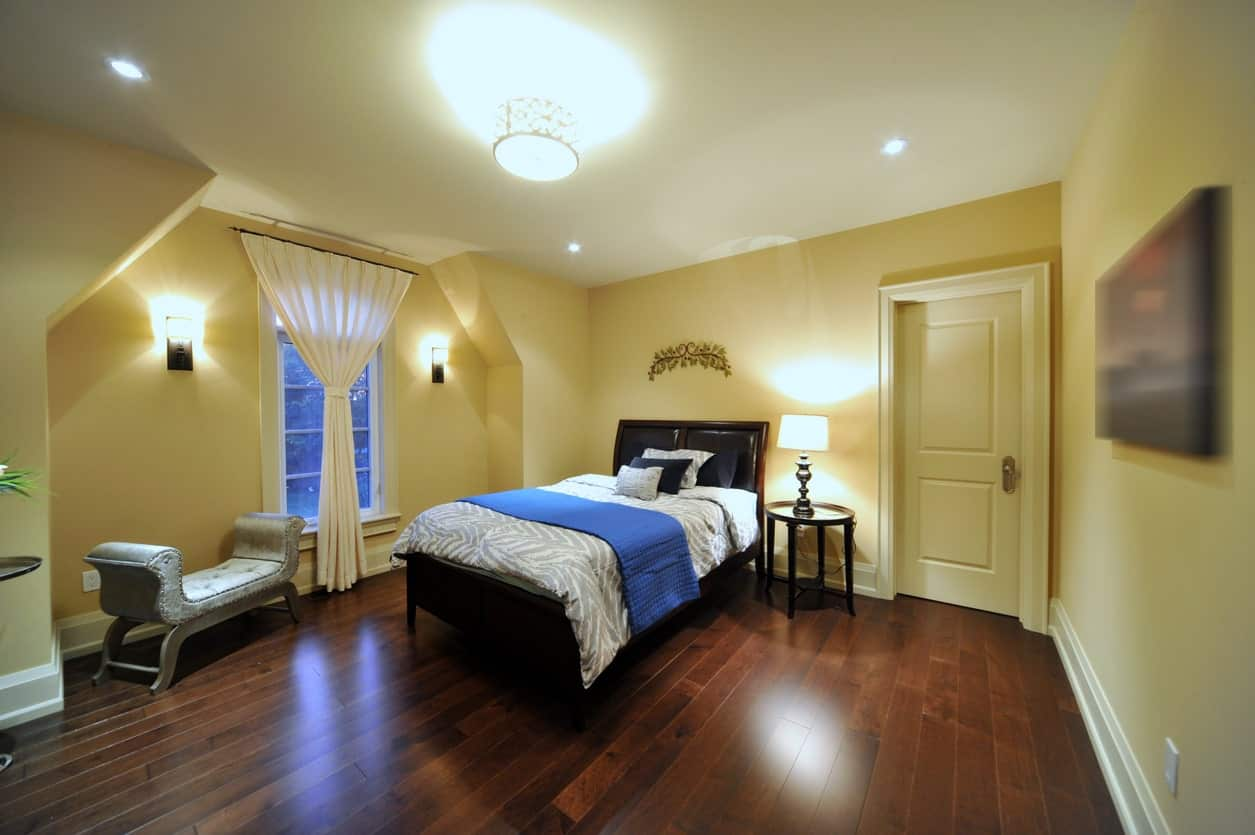 The sleek hardwood flooring of this Transitional-Style primary bedroom is contrasted by the brilliant yellow walls augmented by the warm yellow light of the wall-mounted lights and table lamps that matches the flush mount light on the ceiling.