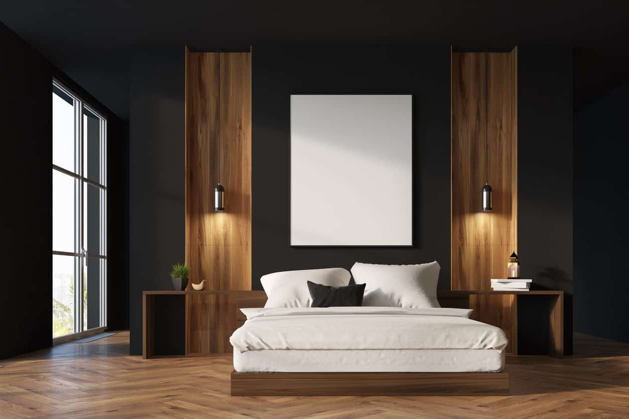 The black wall behind the wooden headboard of the platform bed has a pair of wooden panels that blend in with the bedside tables that are built into the headboard paired with a herring bone flooring.