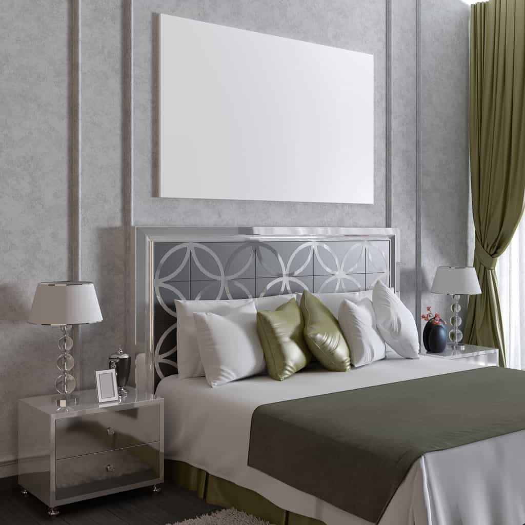 The charming light gray wall behind the modern metallic headboard of the bed is adorned with a blank canvas that imitates the aesthetic of the white hooded table lamps on mirrored bedside drawers.
