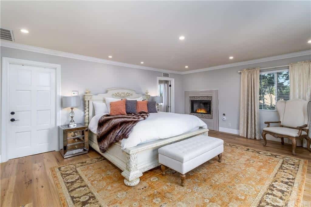 The elegant white wooden traditional bed has carvings that are contrasted by the modern mirrored bedside drawers topped with modern table lamps that lighten up the light gray walls with an embedded modern fireplace.