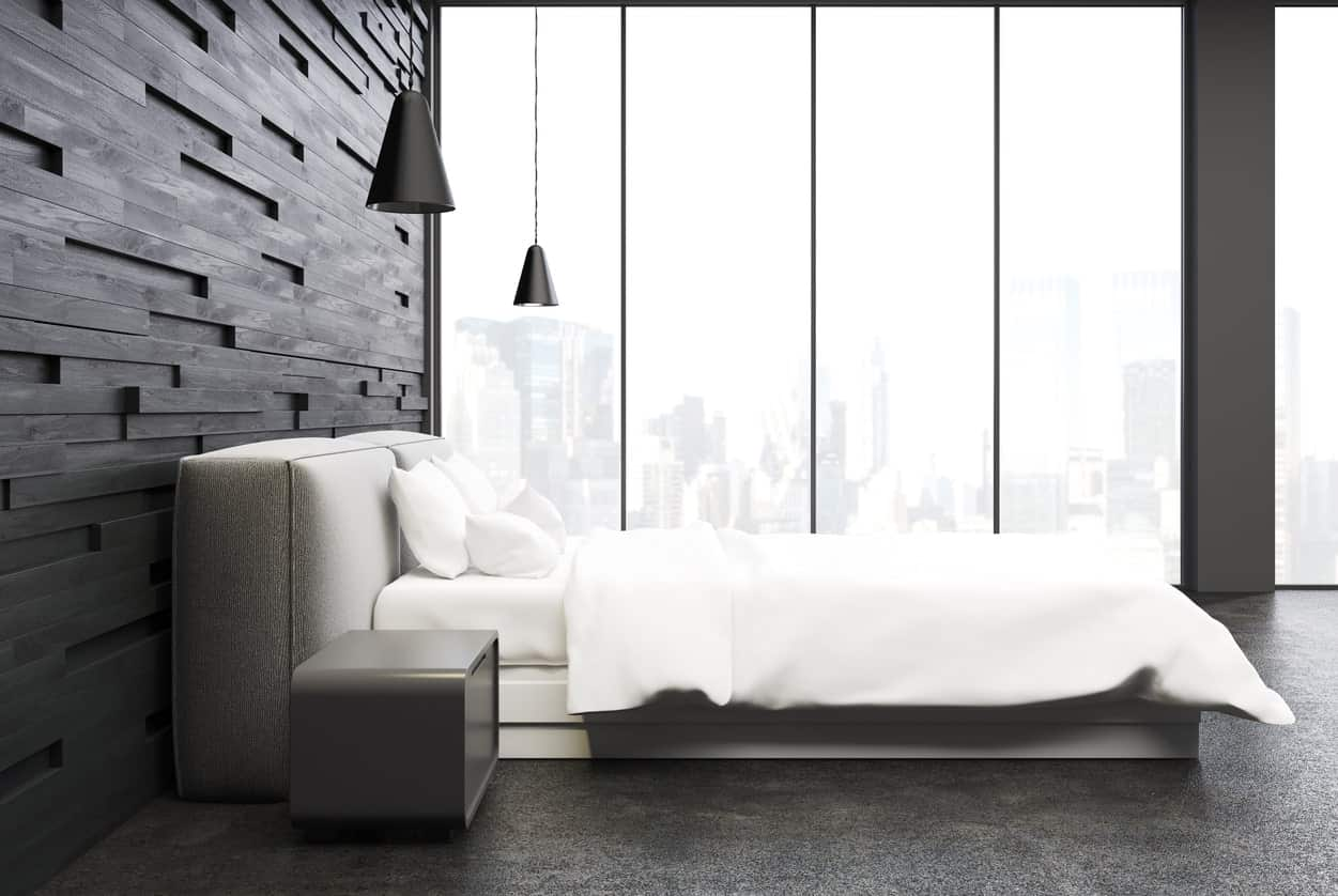 The floor-to-ceiling glass windows of this master bedroom serve as a bright background for the dark elements of the black textured wall behind the cushioned headboard of the platform bed paired with modern bedside tables.