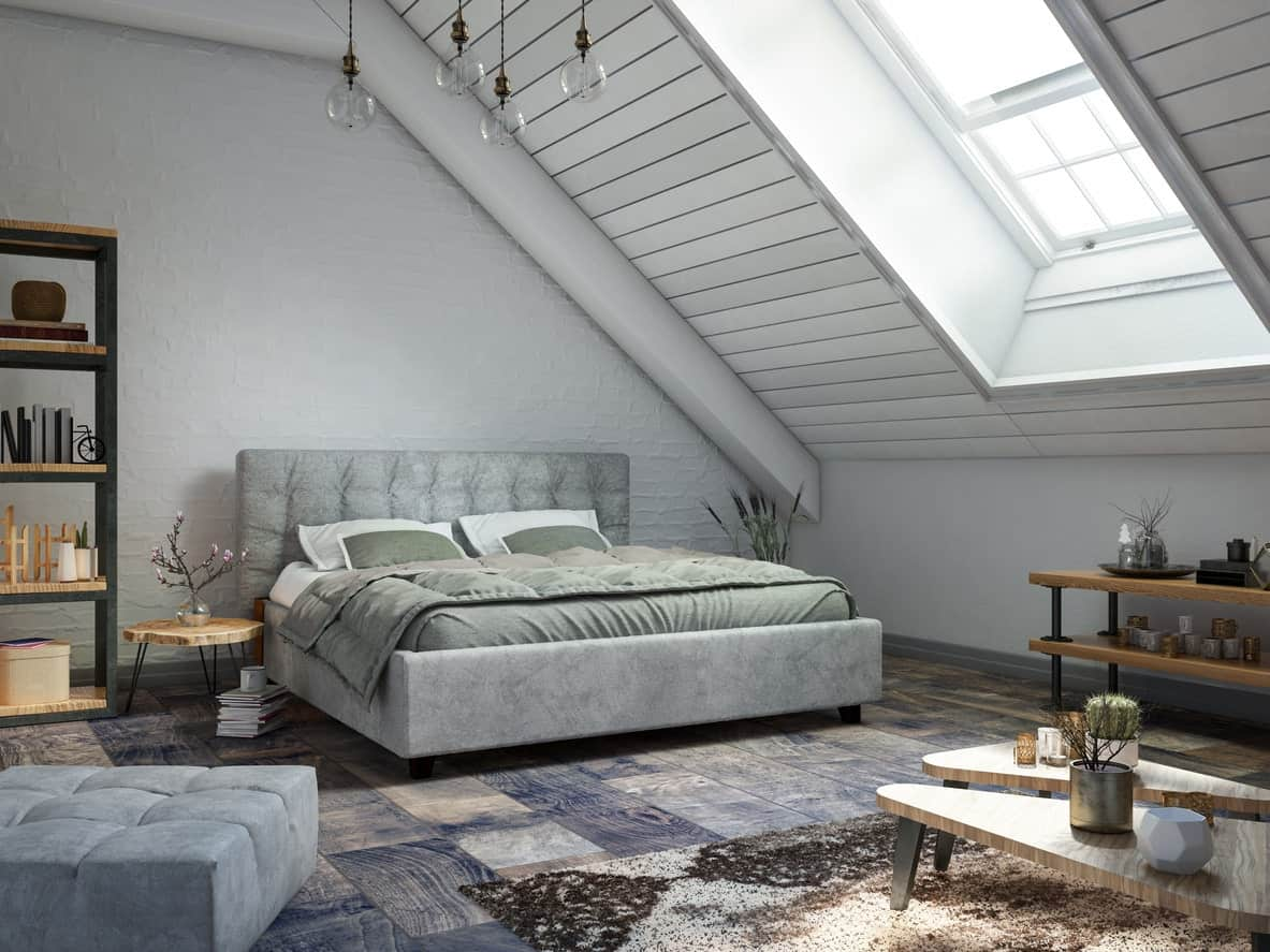This master bedroom has a light gray shed ceiling accented with a skylight that shines down natural light on the gray bed and its flooring that has tiles looking like wood panels.